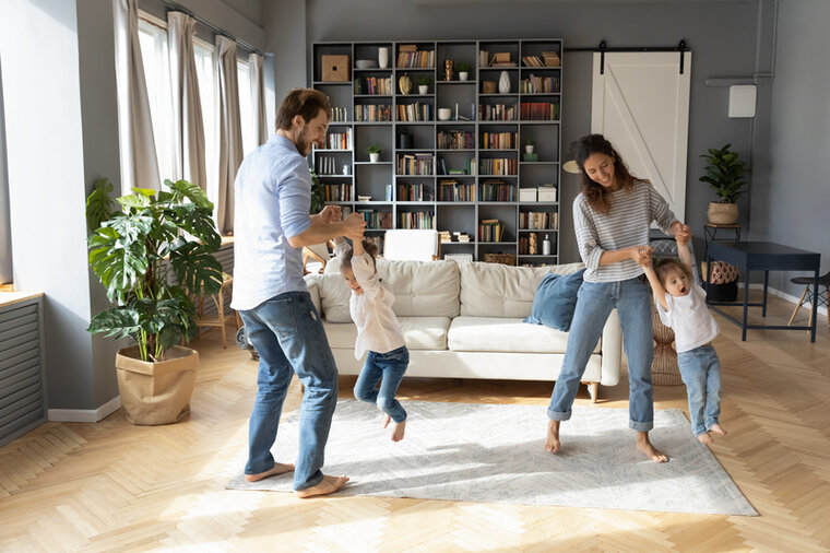 Man and woman dancing with two children in the living room