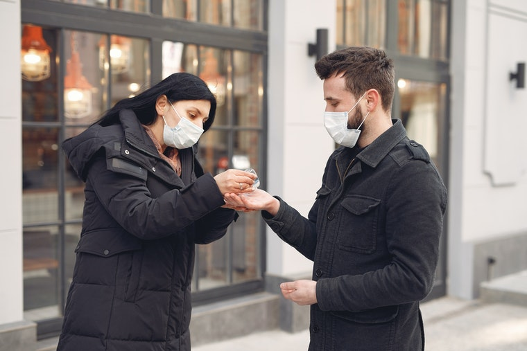 Man and woman in masks using hand sanitizer