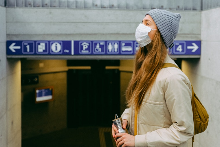 Woman in mask at train station