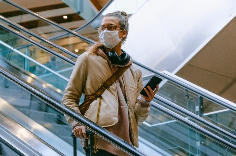 Woman in mask on escalator with mobile phone