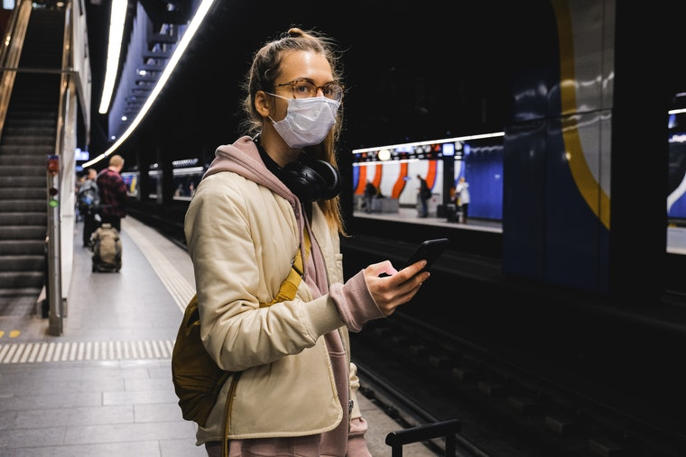 Woman wearing a face mask on a train station platform