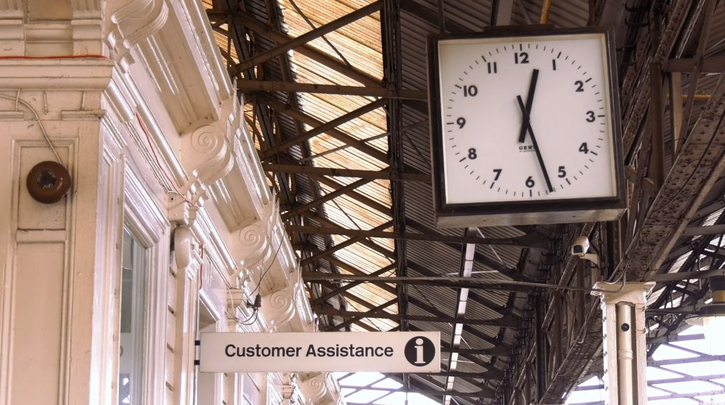 Huddersfield train station with a clock in the foreground and a sign reading Customer Assistance in the background.