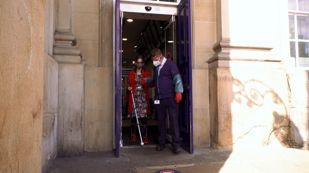 Award-winning disability blogger Chloe Tear receives passenger assistance at Huddersfield train station from a TransPennine Express colleague wearing PPE. They are arm-in-arm walking through the station exit.