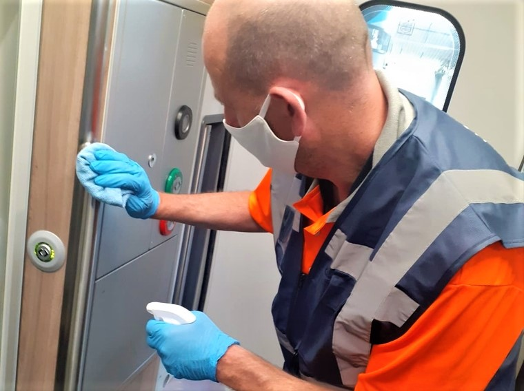 Man wearing mask cleaning train carriage
