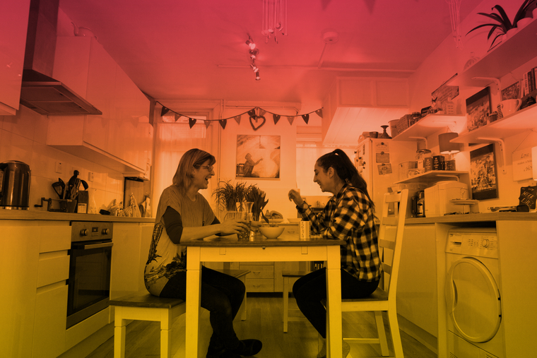 Teenage girl talking to a woman sat at a kitchen table