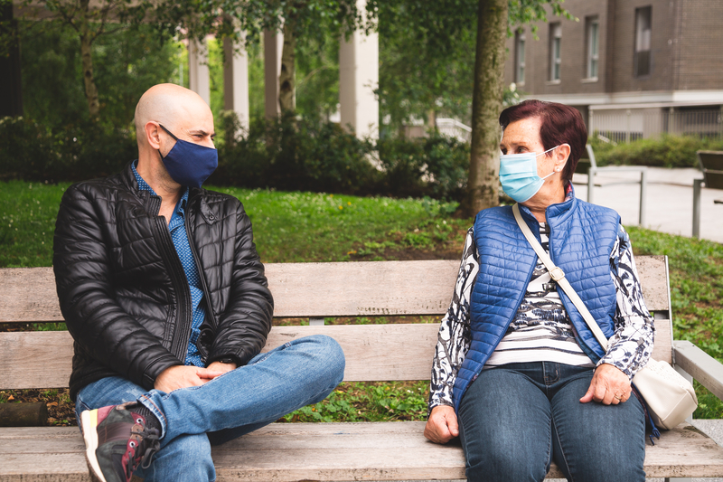 Man wearing face covering talking to elderly woman wearing face covering, both sat on a park bench