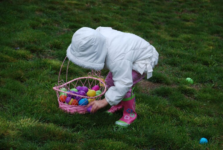 Child collecting easter eggs in garden