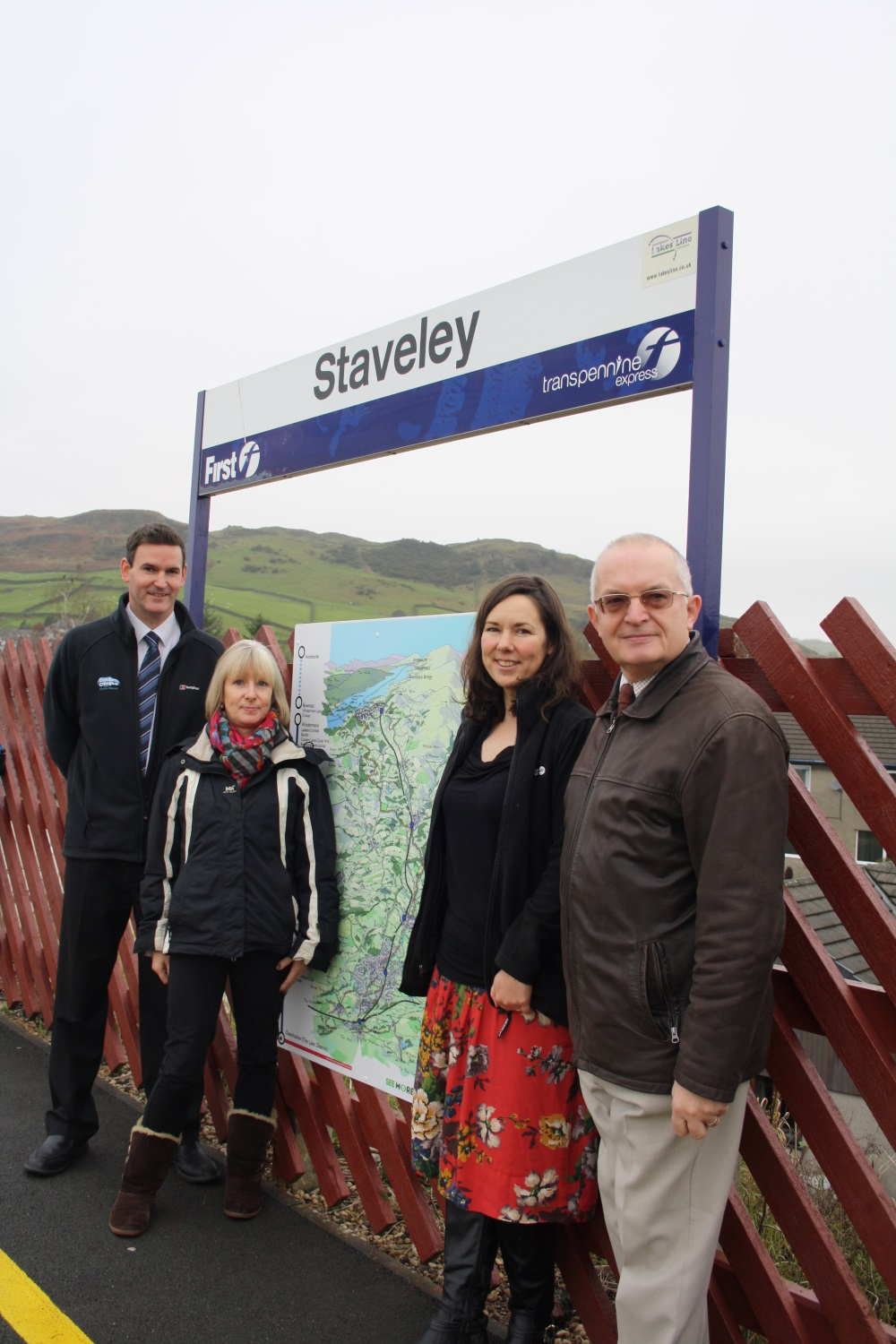 A group of people standing next to a Staveley sign
